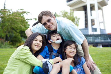 Disabled boy in wheelchair surrounded by family, outdoors by the Space Needle in Seattle Stock Photo