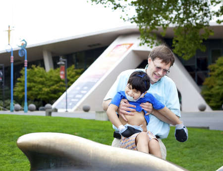 Father helping disabled son play outdoors Stock Photo - 16057860
