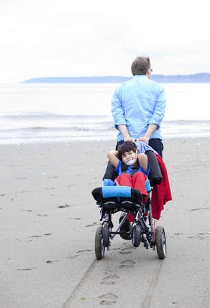 relaxes: Ni�o discapacitado se relaja en silla de ruedas como padre se tira a trav�s de la playa de arena