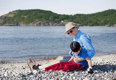 Father sitting on rocky beach playing with disabled son