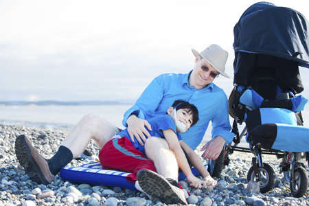 Father sitting on rocky beach playing with disabled son Stock Photo - 16057926