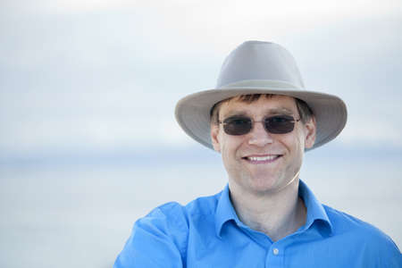 early forties: Handsome man wearing hat and sunglasses in early forties with blurred water background