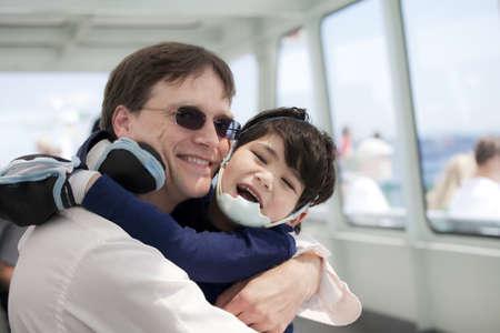 discapacidad: Padre abrazando a hijo discapacitado, ya que montar un ferry Foto de archivo