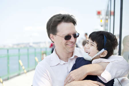 Father hugging disabled son as they ride a ferry boat Stock Photo - 16057856