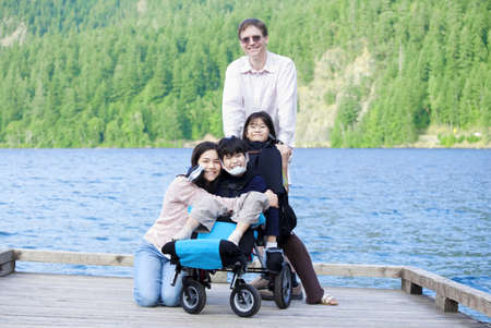 Disabled boy in wheelchair surrounded by family on lake pier Stockfoto