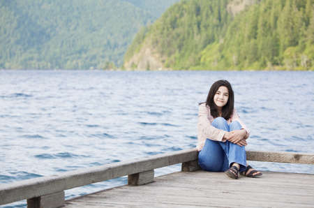 quietly: Young biracial teen girl sitting quietly on lake pier, relaxing