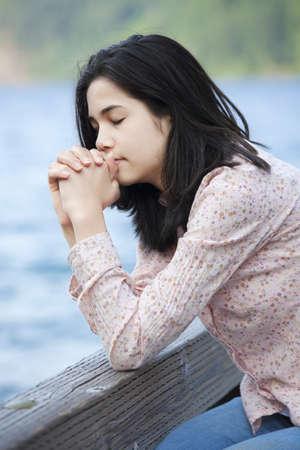 orando: Muchacha adolescente joven que se sienta en silencio en el lago muelle, rezando