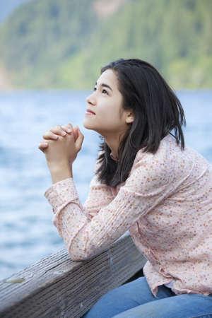 niño orando: Muchacha adolescente joven que se sienta en silencio en el lago muelle, rezando
