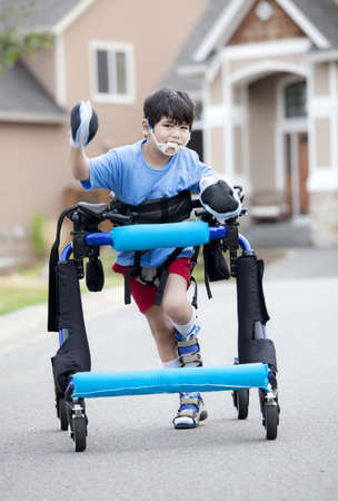 Six year old disabled boy walking in walker down the street Imagens
