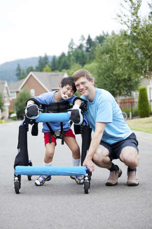 gait: Father kneeling next to disabled son standing in walker Stock Photo