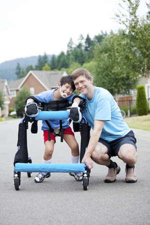 Vader knielend naast gehandicapte zoon staan in walker Stockfoto