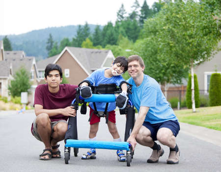 disabled person: Disabled boy in walker surrounded by father and older brother while walking outdoors on street