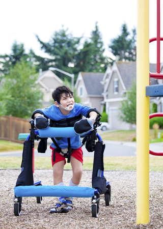 Uitgeschakeld jongen in wandelaar loopt tot een handicap ontoegankelijk speeltuin Stockfoto