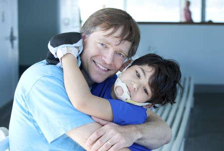 ni�o discapacitado: Desactivado ni�o de cinco a�os de edad, padre d�ndole un gran abrazo Foto de archivo