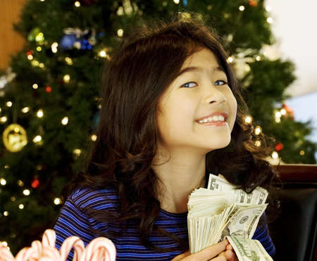prosperous: Little girl holding large amount of cash with Christmas tree in background