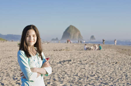 preteens beach: Beautiful preteen girl smiling on beach with Haystack Rock of Cannon Beach, OR in background