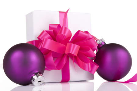moños de navidad: Blanco presente con las cintas rosadas y púrpuras adornos, aislados Foto de archivo