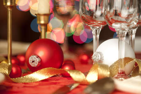 christmas drink: Red and white Christmas ornaments as table decorations, amidst wine glasses Stock Photo