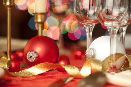 Rode en witte kerst ornamenten als tafeldecoraties, te midden van wijnglazen Stockfoto