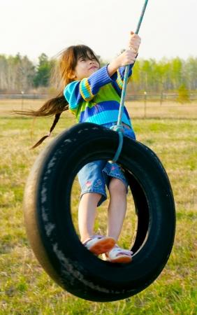 Petite fille balançant sur la balançoire pneu à la campagne Banque d'images