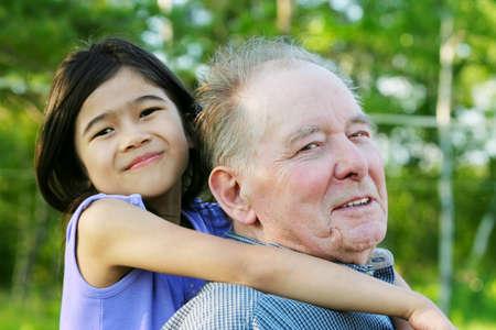 Little asian  girl hugging her caucasian grandfather outdoors, diversity photo