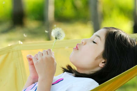 Little girl blowing on a dandelion Imagens
