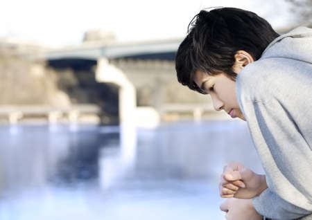 sadly: Teen boy sadly looking out over river, deep in thought