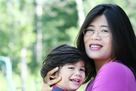 Asian mother lovingly holding her disabled son outdoors in summer. Child is biracial, asian caucasian background. photo
