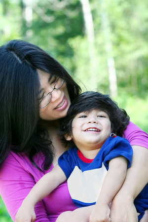 cerebral palsy: Asian mother lovingly holding her disabled son outdoors in summer. Child is biracial, asian caucasian background.