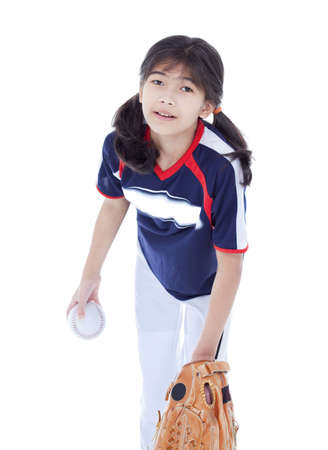 Little biracial asian girl in softball team uniform ready to throw a pitch photo