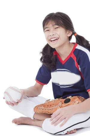 Biracial asian girl holding softball and glove while sitting, isolated photo