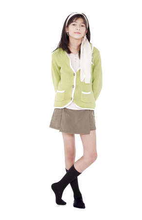 Unsmiling confident young biracial asian girl in green sweater standing, isolated photo