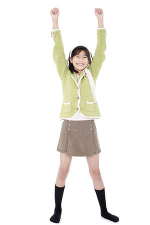 skinny girl: Young asian biracial girl in green sweater and skort standing with arms rasied, happy