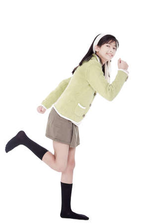 hurrying: biracial asian girl in green sweater and skort in running position, isolated Stock Photo