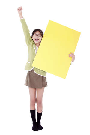 Biracial asian girl in green sweater holidng blank yellow sign, arm cheering in air photo