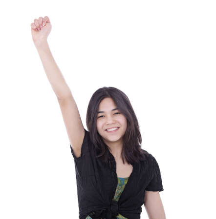 biracial: Confident, young biracial teen girl, raising one arm in air with expression of success.