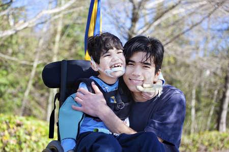 Weinig gehandicapte jongen in een rolstoel knuffelen oudere broer buitenshuis, samen lachend. Kind heeft hersenverlamming.