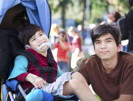 Big brother taking care of disabled little boy in wheelchair outdoors. Child has cerebral palsy. Stock Photo
