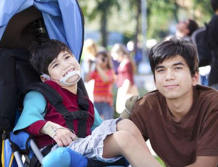 Grote broer de zorg voor gehandicapte jongetje in rolstoel buiten. Kind heeft hersenverlamming.