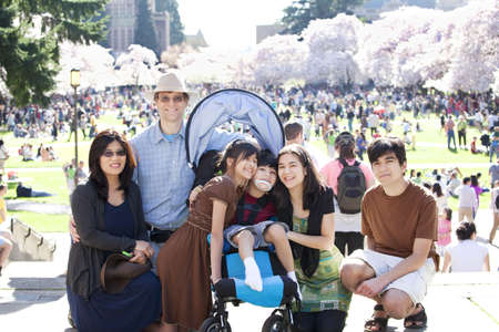immobility: Large multiracial family in crowd with disabled child in wheelchair. Flowering cherry trees in background. Stock Photo