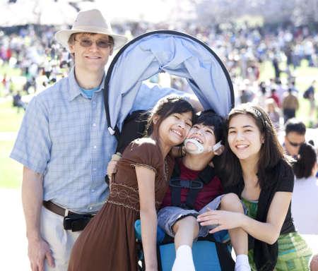 Grote multiraciale familie in menigte met gehandicapt kind in rolstoel. Bloeiende kersenbomen op de achtergrond. Stockfoto