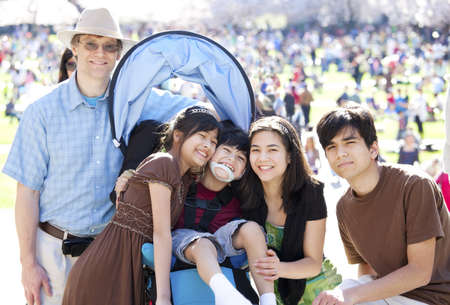 cerebral palsy: Large multiracial family in crowd with disabled child in wheelchair. Flowering cherry trees in background. Stock Photo