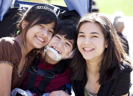 Uitgeschakeld biracial jongen in een rolstoel, omringd door zijn grotere zussen, glimlachend. Kind heeft hersenverlamming. Stockfoto