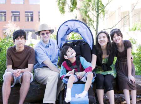 Father sitting with his biracial children and disabled son in wheelchair. Child has cerebral  palsy. Stock Photo