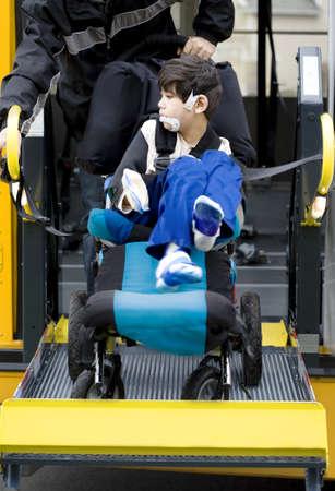 transporte escolar: Disabled niño de seis años de edad en el autobús ascensor para sillas de escuela, ir a la escuela