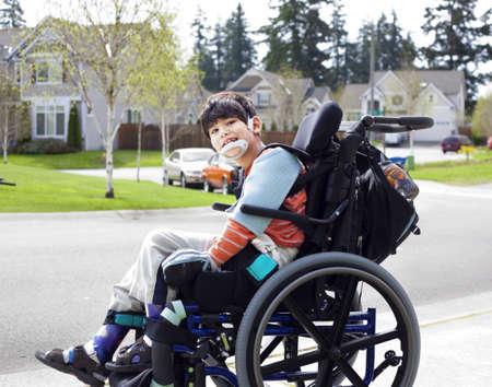 Gelukkig gehandicapte zes jaar oude jongen te wachten op de stoep in rolstoel kind heeft hersenverlamming