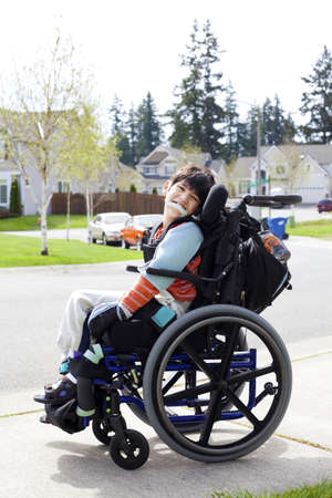 needs: Happy disabled six year old boy waiting on sidewalk in wheelchair  Child has cerebral palsy