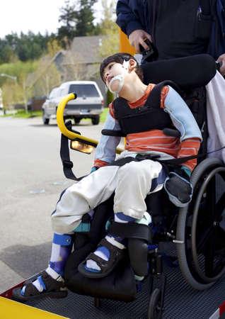 ni�o discapacitado: Disabled ni?o de seis a?os de edad en el autob?s ascensor para sillas de escuela, ir a la escuela