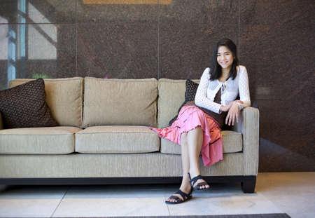 sandalias: Niña adolescente birracial descansando en un sofá elegante