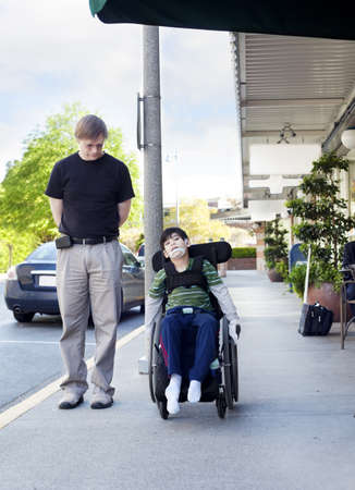 Father walking next to disabled six year old son in wheelchair through town  Son has cerebral palsy  photo